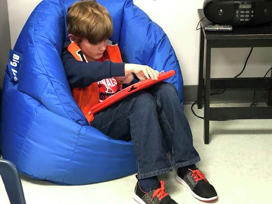 Kieran Strasen, a second grade student at Leclaire Elementary, works on an assignment while in a bean bag chair. Photo: Julia Biggs | The Intelligencer