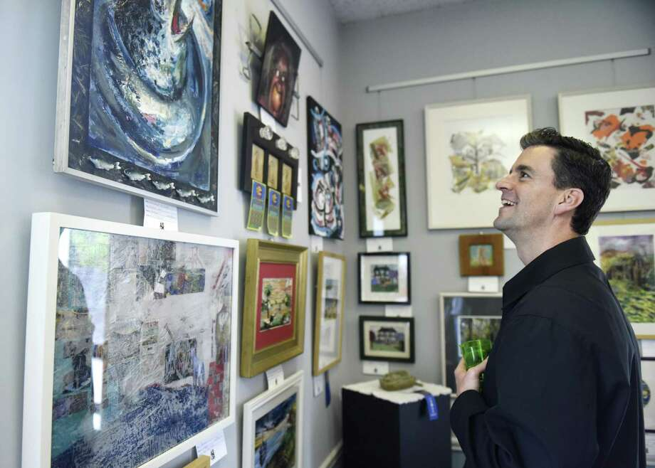 Old Greenwich's Kevin Judge looks at mixed media entries during the opening reception of the Art Society of Old Greenwich's Spring Exhibit and Sale at the Greenwich Botanical Center in the Cos Cob section of Greenwich, Conn. Sunday, May 5, 2019. 83 entries in mediums including oil painting, acrylic painting, watercolor, photography, mixed media, drawing, and sculpture are displayed at the Botanical Center through May 23. Photo: Tyler Sizemore / Hearst Connecticut Media / Greenwich Time