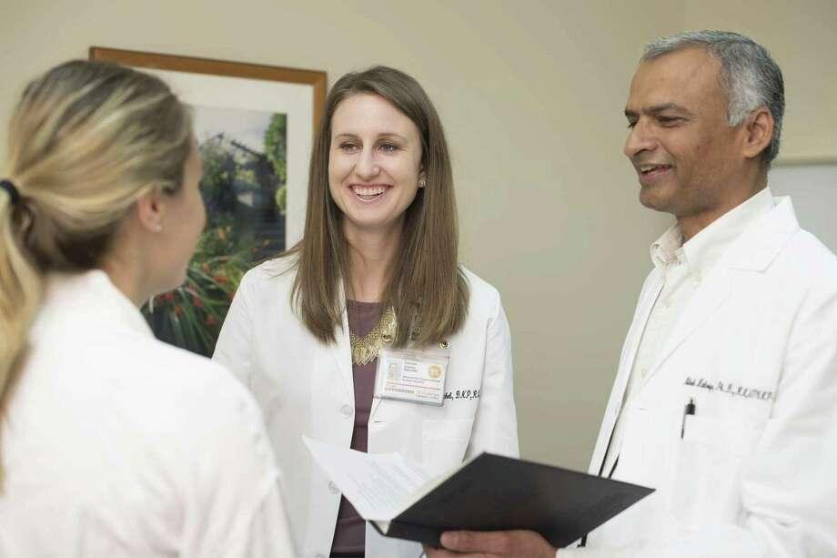 APRN Fellows Brie Urschel and Nilesh Kalariya interact with a patient during their clinical rotations.