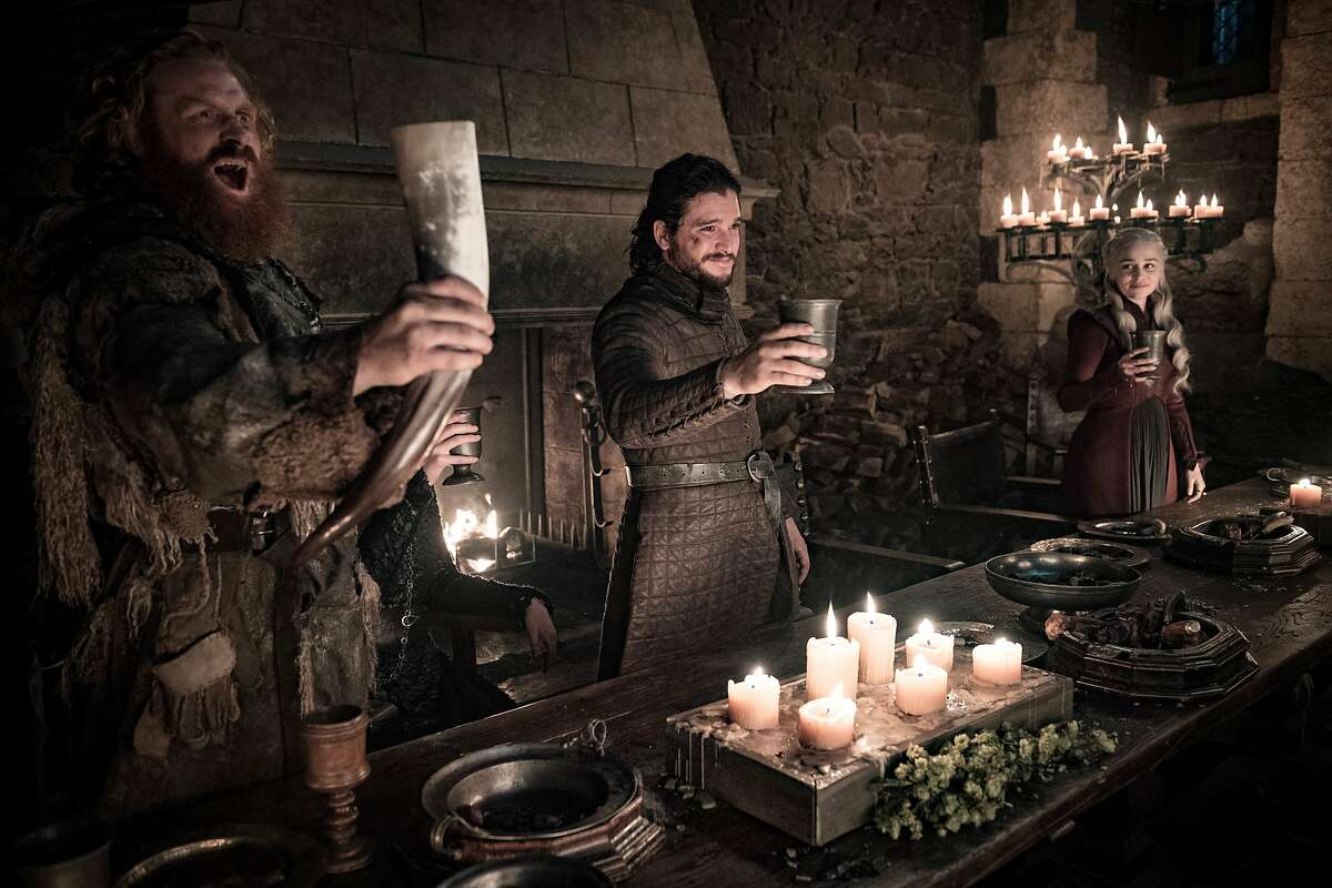 """This image released by HBO shows Kristofer Hivju, from left, Kit Harington and Emilia Clarke in a scene from """"Game of Thrones."""" fans got a taste of the modern world when eagle-eyed viewers spotted a takeout coffee cup on the table during a celebration in which the actors drank from goblets and horns. The characters Daenerys and Jon did not react to the out of place cup in Sunday's episode. Many viewers complained the show should have caught the gaffe, which turned into an enduring meme on Monday.(Helen Sloan/HBO via AP)"""