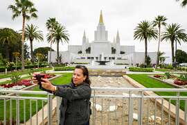 Mary June Burns, a member of the Church of Jesus Christ of Latter-day Saints takes a selfie with the Mormon Temple in Oakland, California, on Monday, May 6, 2019. The interior recently completed extensive renovations.