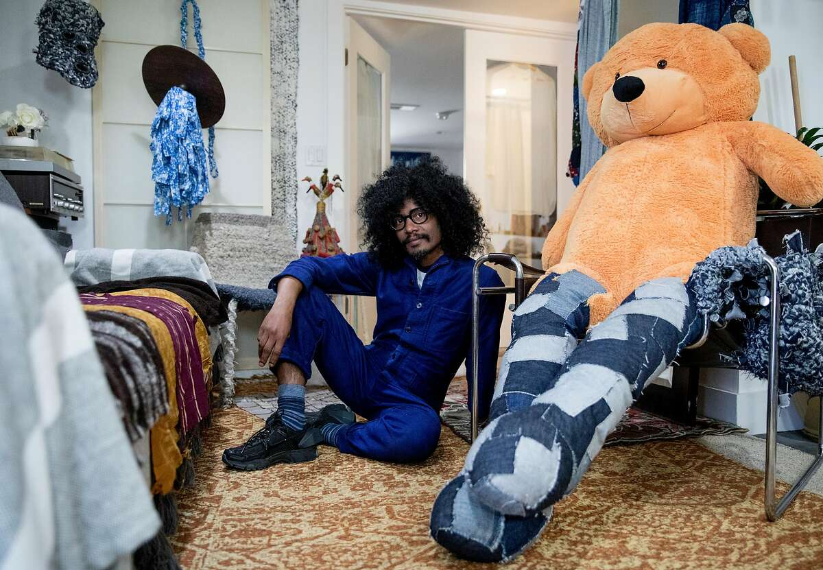 Textile artist Llane Alexis poses for a portrait among his finished and in-progress pieces inside his home and studio space in San Francisco, Calif., Saturday, April 27, 2019.