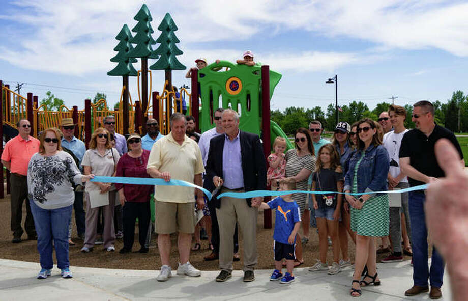 Surrounded by people who contributed to the construction of the Roy M. Schon Park, Mayor of Glen Carbon, Robert Jackstadt, cuts the ribbon at the grand opening in Glen Carbon. Photo: Breanna Booker | The Intelligencer