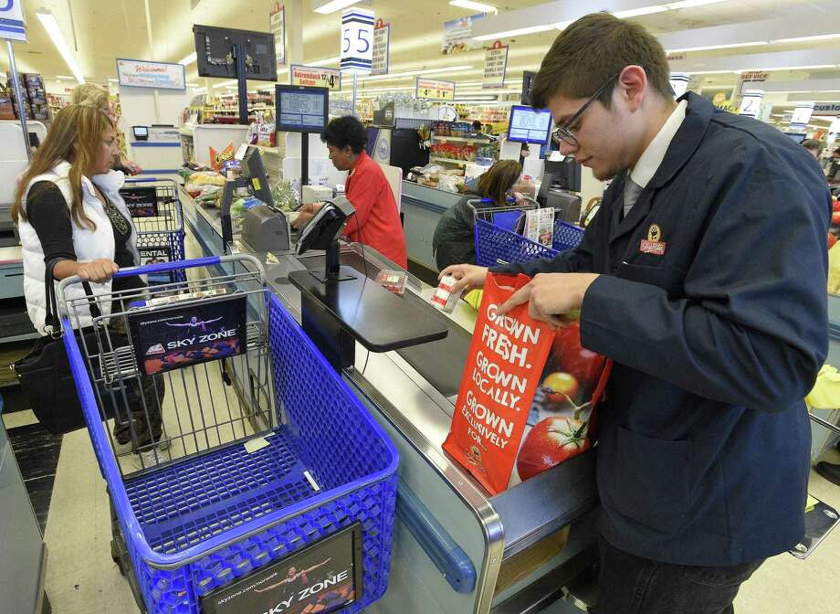 Jason Najera, a customer service agent at ShopRite, bags a customer's order in a reusable shopping bag. Photo: Matthew Brown / Hearst Connecticut Media / Stamford Advocate