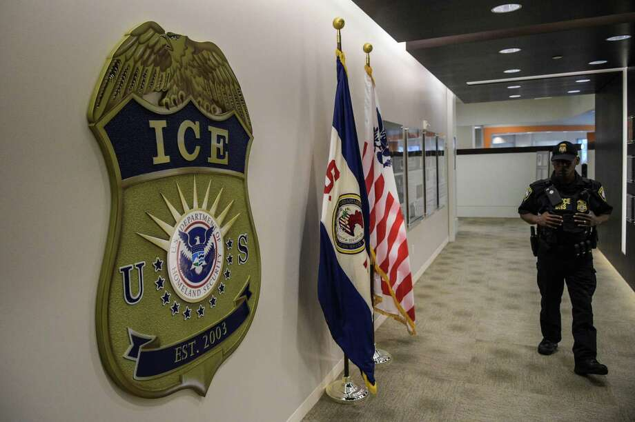 A law enforcement officer walks past ICE logo at the U.S. Immigration and Customs Enforcement headquarters in Washington in 2017. Photo: Washington Post Photo By Salwan Georges. / The Washington Post