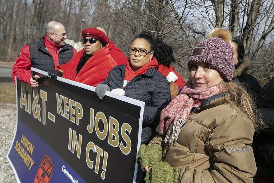 AT&T employee Lucia Coelho of Prospect, right, stands with co-workers affected by the planned closure of several local AT&T call centers. (Dave Zajac/Record-Journal via AP) Photo: Dave Zajac / Contributed Photo / Dave Zajac/Record-Journal via AP
