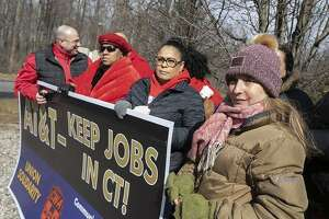 AT&T employee Lucia Coelho of Prospect, right, stands with co-workers affected by the planned closure of several local AT&T call centers. (Dave Zajac/Record-Journal via AP)