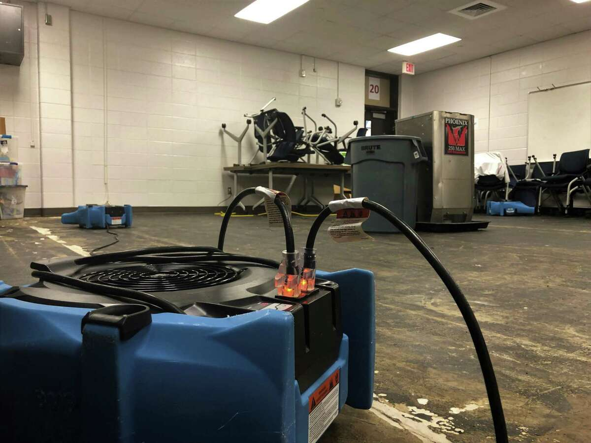 Fans and humidifiers scattered around the flooded areas in Kingwood High School, including the weight room, the hallway and a classroom, on May 6 in Kingwood.