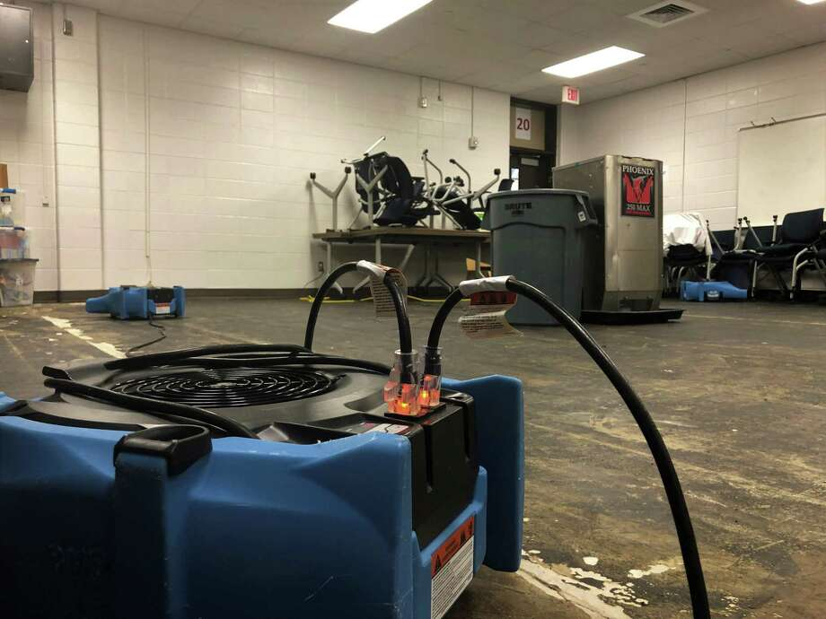 Fans and humidifiers scattered around the flooded areas in Kingwood High School, including the weight room, the hallway and a classroom, on May 6 in Kingwood. Photo: Nguyen Le / Staff Photo