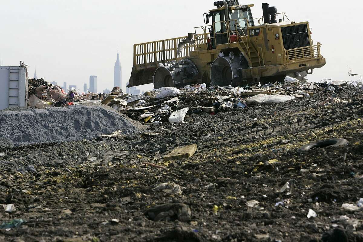 A large tractor moves trash and garbage around on top of an area at the 1-E landfill in Kearny, N.J., Monday, Oct. 6, 2008. The Kearny site is among 21 landfills in New Jersey that convert methane gas produced by decomposing trash into electricity, according to the state Board of Public Utilities. (AP Photo/Mike Derer)