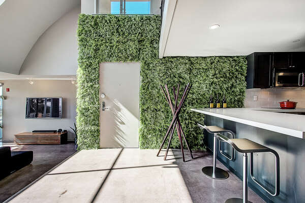 A penthouse condo in the inner-Mission with a view, lofty ceiling, and faux fern wall: this unique pad asks $1.098 million.
