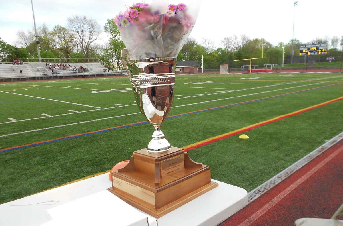 The Kuchta Cup, presented annually to the winner of the girls lacrosse game between McMahon and Norwalk, waits, with flowers for the Kuchta family, before the game at McMahon's Jack Casagrande Field on May 6, 2019. McMahon won 16-6.