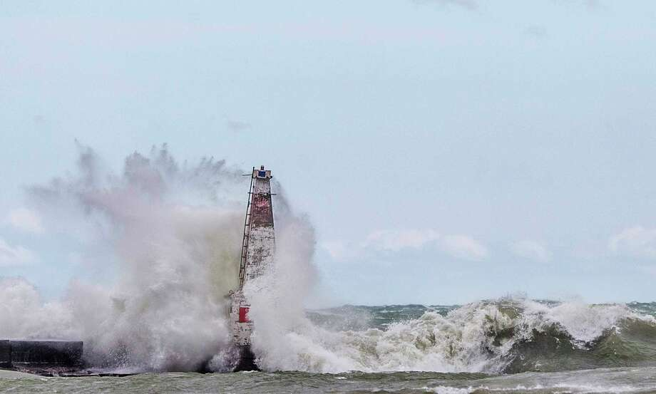 FILE - In this April 6, 2017 file photo, big waves crash against a breakwater light as strong winds create dangerous conditions on Lake Michigan, at Washington Park in Michigan City, Ind. Federal officials predict surging water levels across the Great Lakes and record highs in Lakes Superior and Erie over the next six months. A report Monday, May 6, 2019 from the U.S. Army Corps of Engineers says the lakes have been rising steadily for several years and are getting an extra boost as winter's melting snow mingles with recent heavy rainfall. It's a remarkable turnaround from early this decade, when lake levels were slumping and some hit record lows. (Robert Franklin/South Bend Tribune via AP, File) Photo: Robert Franklin / South Bend Tribune