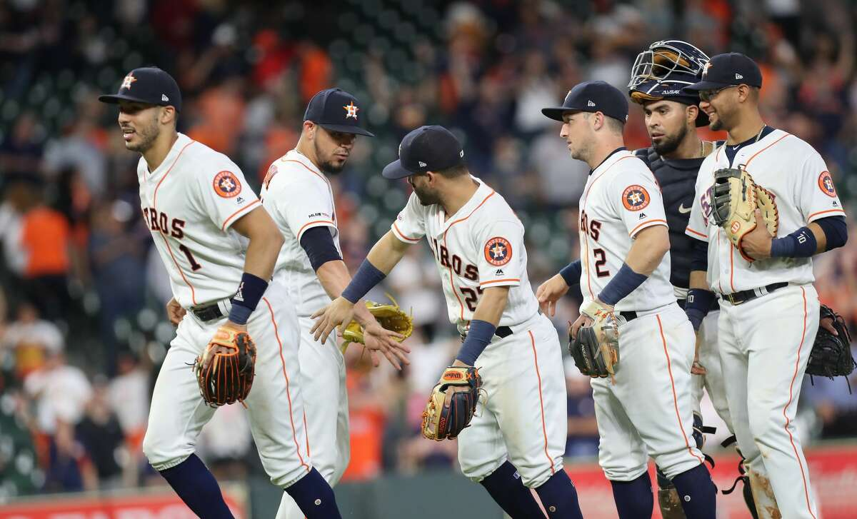 Houston Astros players congratulates Houston Astros relief pitcher Roberto Osuna (54) after defeating the Kansas City Royals in a MLB baseball game at Minute Maid Park Monday, May 6, 2019, in Houston.