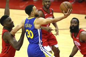 Golden State Warriors guard Stephen Curry (30) drives to the basket between Houston Rockets center Clint Capela (15) and guard James Harden (13) during the first half of Game 4 of the NBA Western Conference semifinals at Toyota Center on Tuesday, May 7, 2019, in Houston.