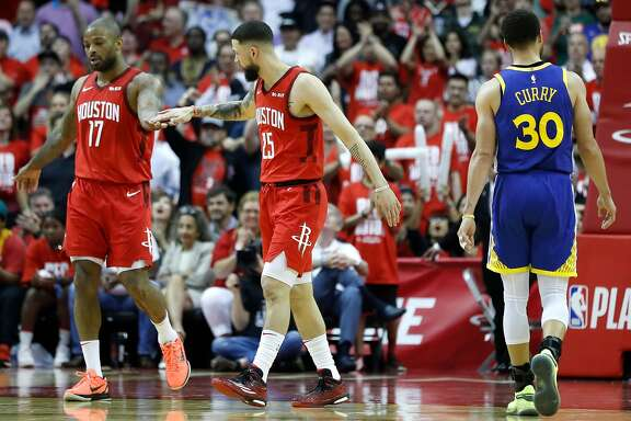Houston Rockets forward PJ Tucker (17) and guard Austin Rivers (25) high five as Golden State Warriors guard Stephen Curry (30) walks back up the court during the second half of Game 4 of a NBA Western Conference semifinal playoff game at Toyota Center, in Houston , Monday, May 6, 2019.