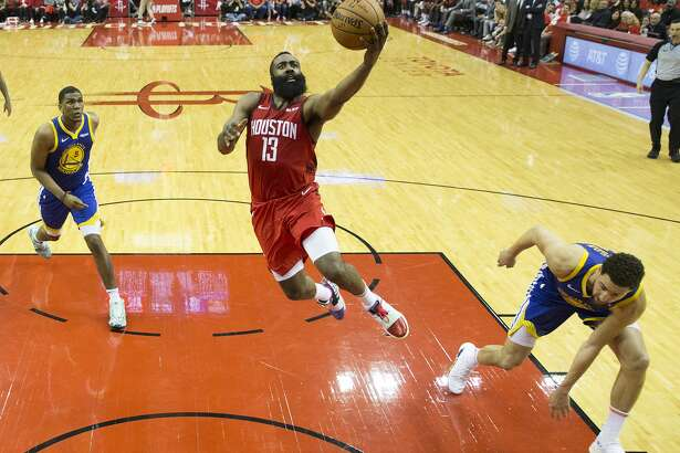 Houston Rockets guard James Harden (13) drives to the basket for a layup past Golden State Warriors center Kevon Looney (5) and guard Klay Thompson (11) during the second half of Game 4 of the NBA Western Conference semifinals at Toyota Center on Monday, May 6, 2019, in Houston.
