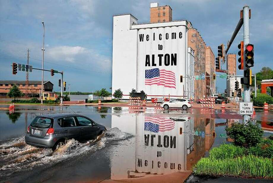 A vehicle drives on Monday through Mississippi River flood water in downtown Alton. Flooding from the Mississippi River closed streets in downtown, forced the closure of Argosy Casino and flooded the basements of several businesses. The Mississippi River crested Monday, almost 14 feet above flood stage. The red painted line beneath the American flag on the grain silos denotes the height of flood water in 1993. Photo: David Carson | St. Louis Post-Dispatch Via AP