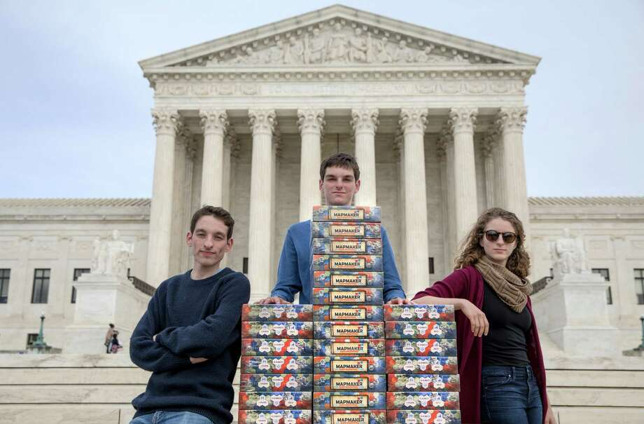 Josh Lafair, center, stands with siblings Louis and Rebecca, and the board game they created, Mapmaker: The Gerrymandering Game, outside the Supreme Court on March 26, the day the court heard oral arguments in two gerrymandering-related cases. Photo: Photo For The Washington Post By Evelyn Hockstein / For The Washington Post