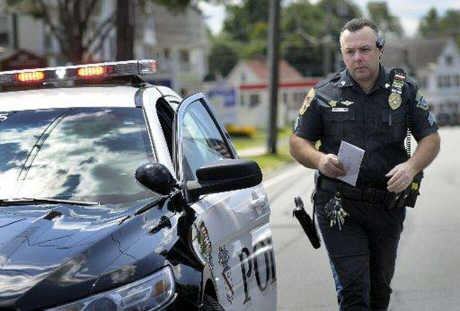 Danbury police Sgt. Rory DeRocco issues a ticket to a driver who went through a red light on North Street in Danbury, Friday, August 7, 2015. Photo: Carol Kaliff