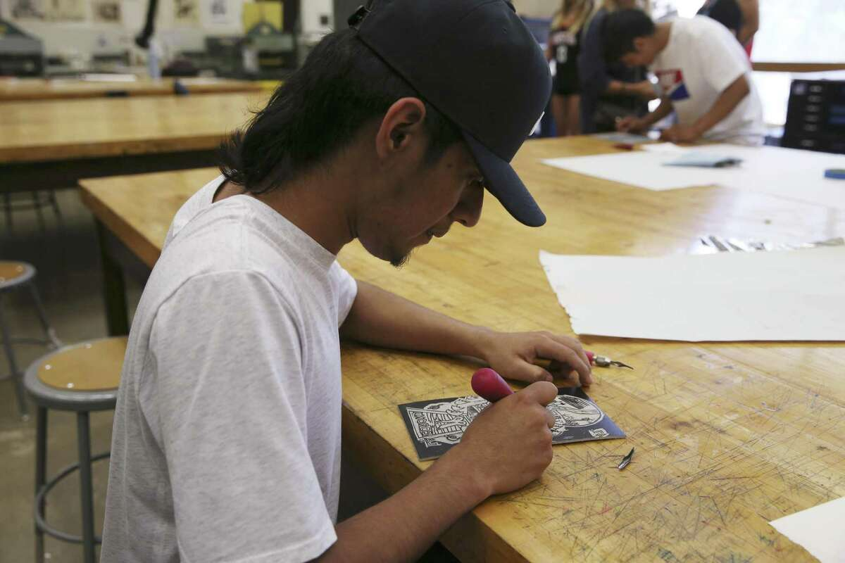 Samuel Rivas, 18, of El Salvador, works on an linocut during a workshop at the University of Texas at San Antonio. A group of young migrants receiving help from Posada Guadalupe, which assists homeless migrants, have been taking art lessons from some of the city's best-known artists.