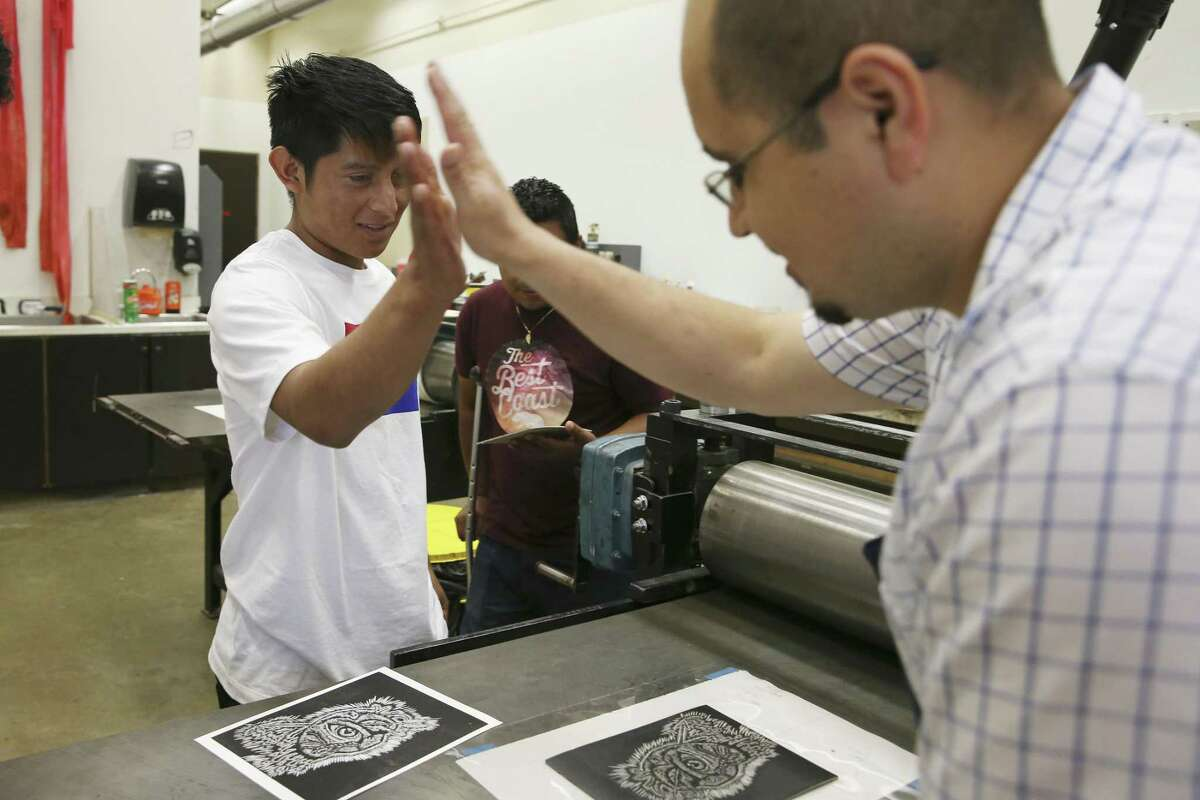"""Walter Rodriguez, 18, left, high fives Juan de Dios Mora during a printmaking class at UTSA. Rodriguez titled his piece, """"Sentimiento,"""" which means """"Feeling"""" in English. In the center of the heart in his print is an eye. """"The essential is invisible through the eye,"""" Rodriguez said of his print."""