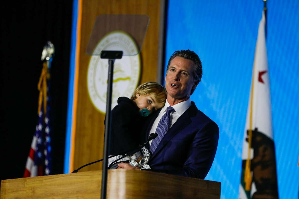 Governor Gavin Newsom holds his son Dutch Newsom, 2, during his inauguration speech after his son ran up on stage in Sacramento, California, on Monday, January 7th, 2019.