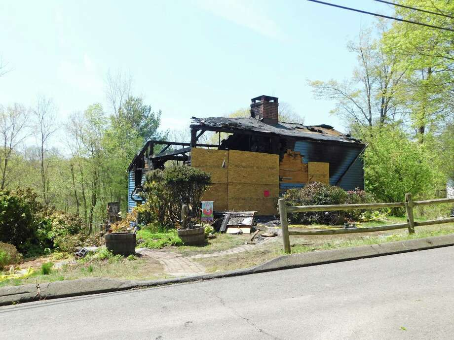 The remains of the house at 5 Farrell Road after a fire ripped through it during the early morning hours of May 7, 2019. Photo: Kendra Baker / Hearst Connecticut Media / NikonCoolpix
