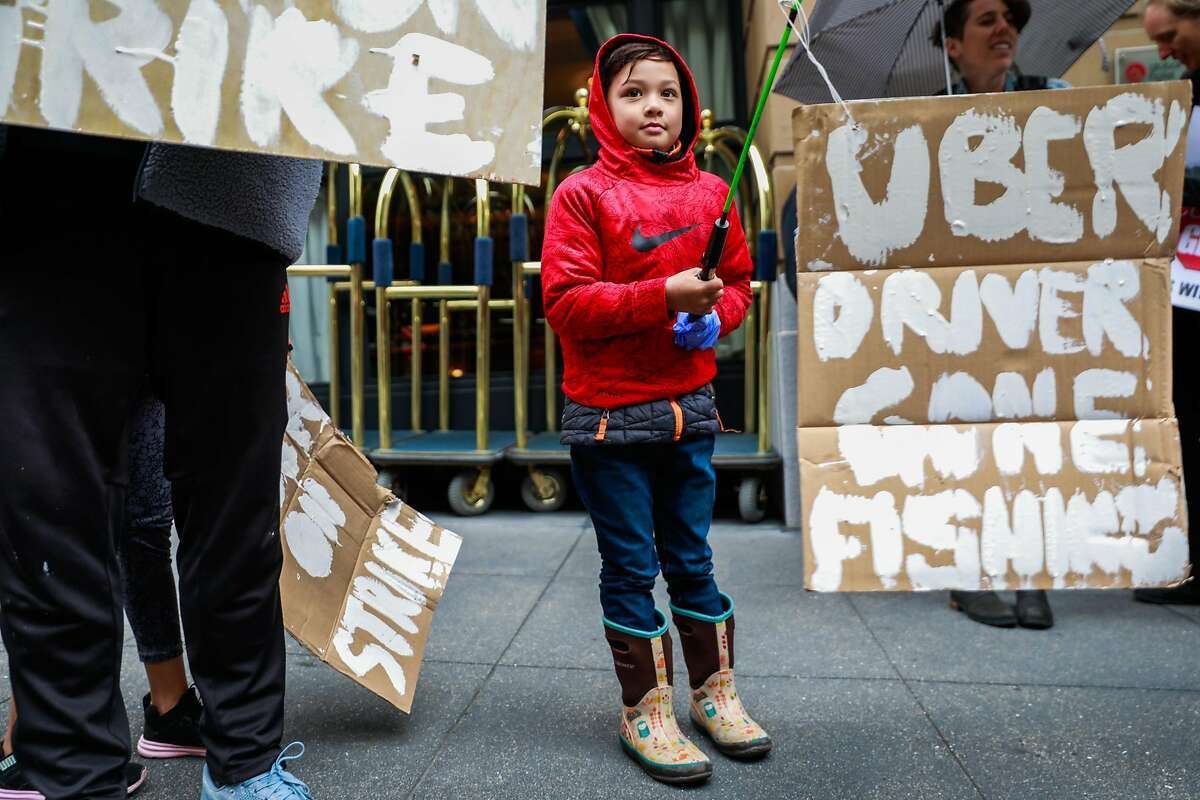 """Cameron McConnell, 7 holds up a homeade sign that says """"Uber Driver Gone Fishing"""" as he stands alongside his father Gregory McConnell (left) during a protest against Lyft's paycuts and their plan to go public on Friday in San Francisco , California, on Monday, March 25, 2019. Drivers argue that their share has been cut significantly and that they are the backbone of the company."""
