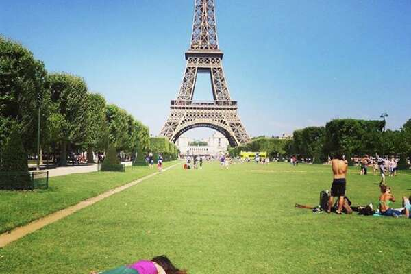 "Stephanie Leigh visits the Eiffel Tower in Paris in her own macabre way. The artist's ""Stef Dies"" project on Instagram, which shows her playing dead at famous sites, mocks selfie culture. (Photo courtesy of Stephanie Leigh)"