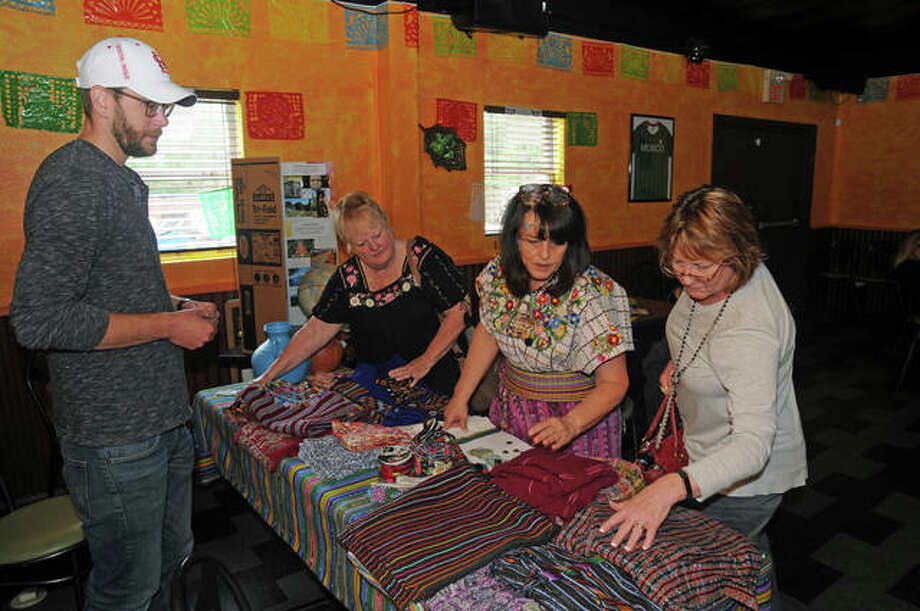 """Small Town - Big World"" visitors examine Mexican fabrics at Little Mexico Restaurant in Alton. Photo: David Blanchette 