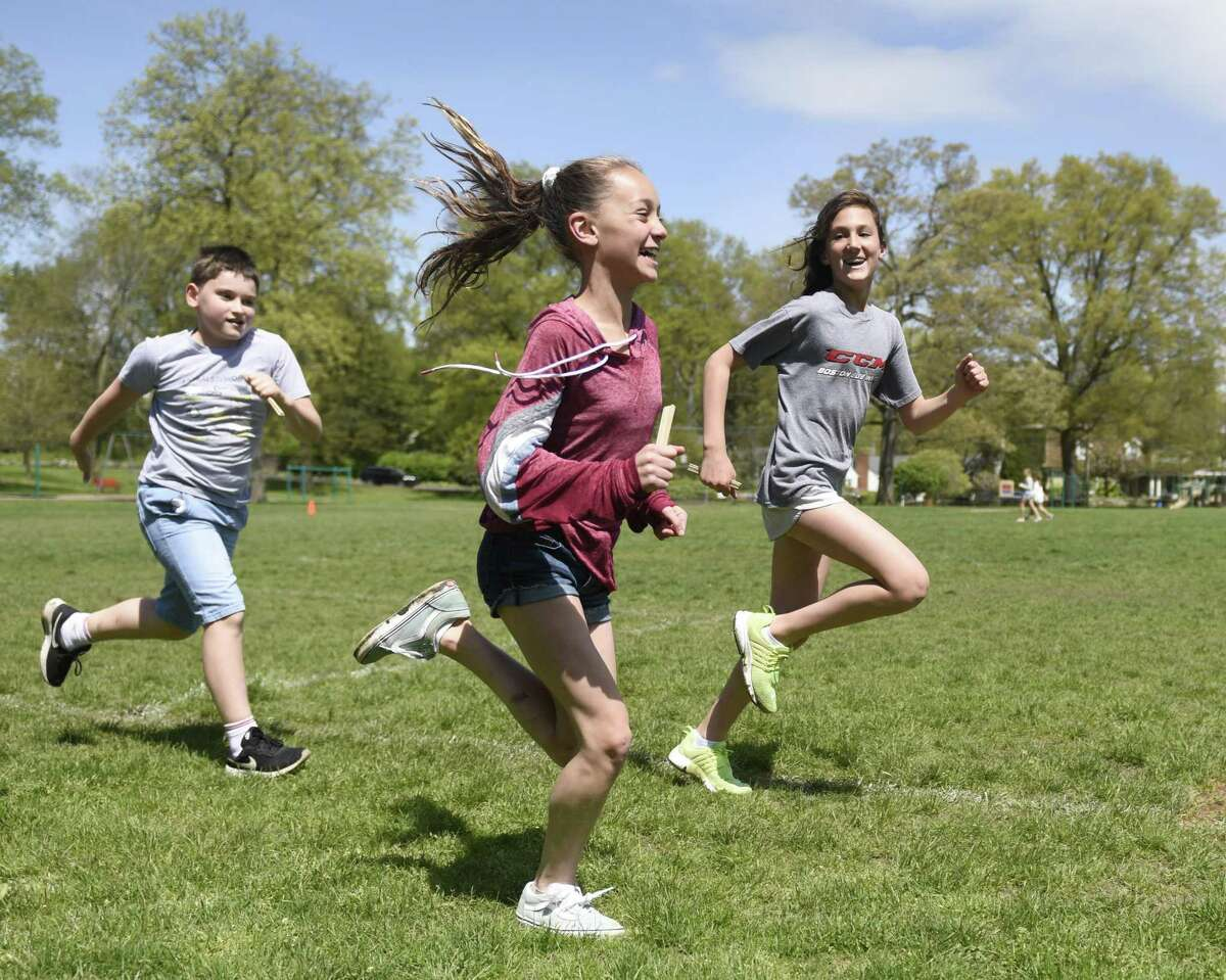 Fifth-graders Tom Gray, left, Julia Lattuada, center, and Chloe Cleaves run laps to raise money for pediatric brain cancer research at Yale New Haven Hospital at Riverside School in the Riverside section of Greenwich, Conn. Monday, May 6, 2019. In the second-annual Run for Life, students run laps during gym class and recess while gathering sponsors agreeing to pay them a certain amount for every lap they complete.