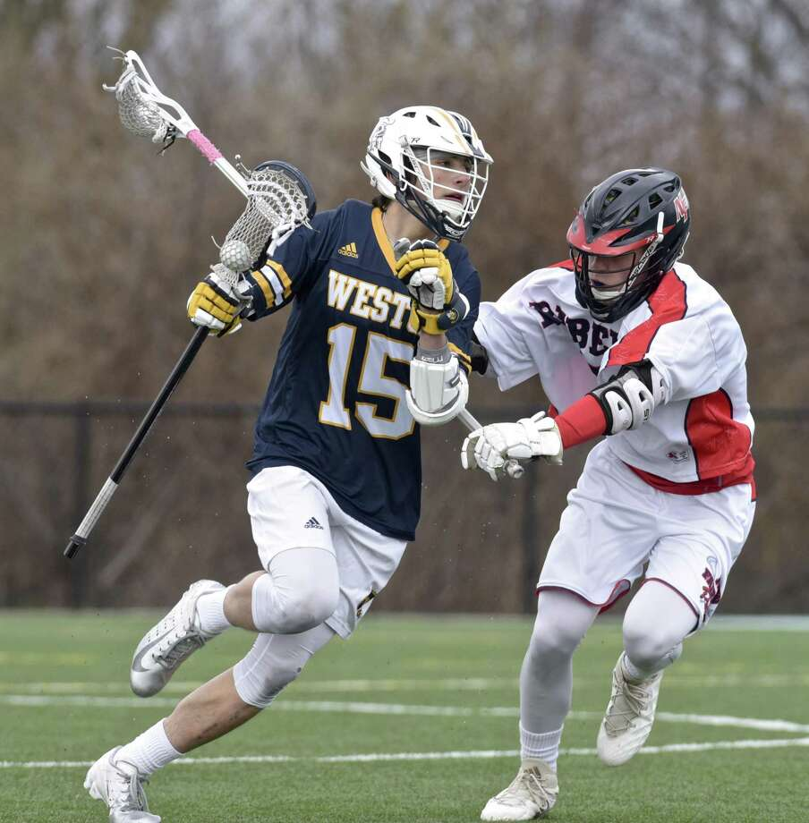 Weston's James Goetz, left, moves against New Fairfield's Will Enright on April 19, 2018. Photo: H John Voorhees III / Hearst Connecticut Media / The News-Times