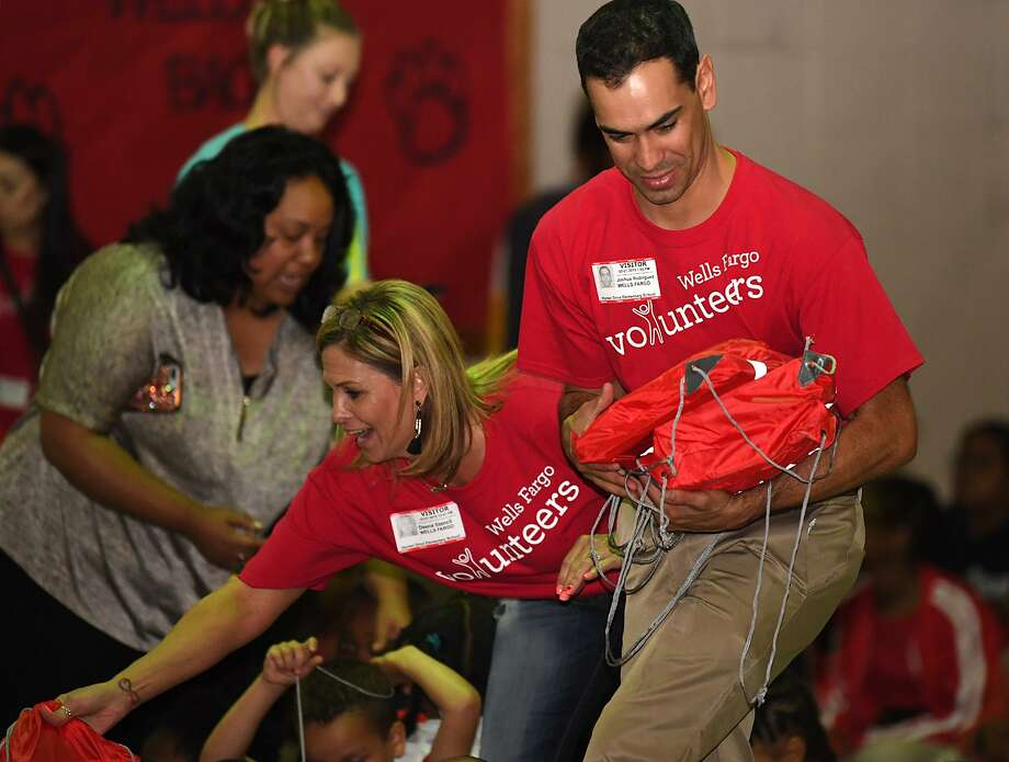 Wells Fargo's Joshua Rodriguez hands out a bag of books to a Homer Elementary student on Monday. The bank donated 20 books to each student after learning about the school's principal Belinda George using the internet to read to her students on Tuesday nights. Photo taken Tuesday, 5/7/19 Photo: Guiseppe Barranco/The Enterprise, Photo Editor / Guiseppe Barranco ©