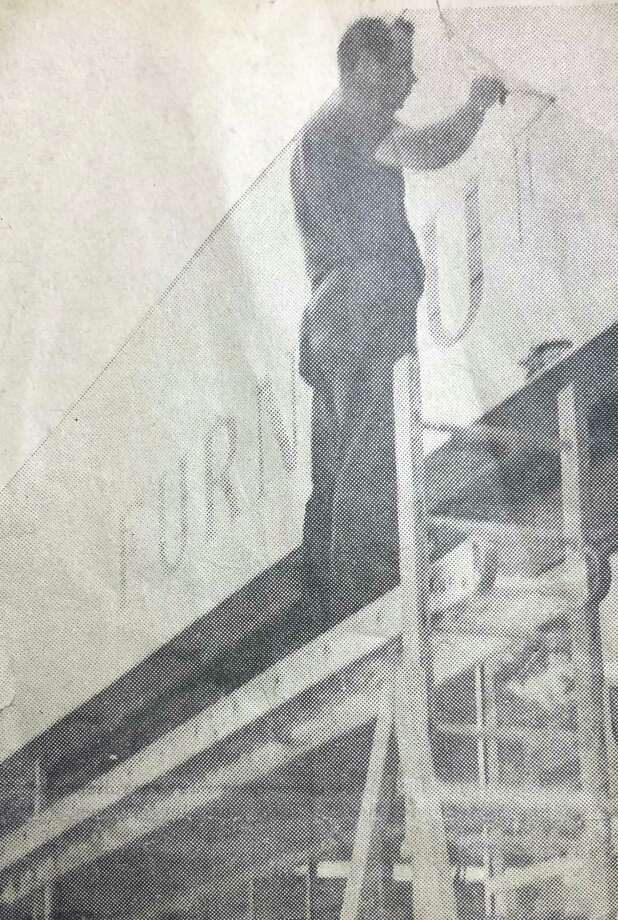 """Signs today aren't made as they were in the past. Years ago, signs and billboards were hand-painted, as shown in this circa 1970s photo printed in The New Milford Times. The photo is of George Pineman, longtime owner of Pineman Sign Co. on East Street in New Milford, adding the final touches to the sign above Family Furniture Company, housed in the former W.T. Grant Co. store on Main Street, which was the anchor store of the building that now houses Domino's in town. The proprietor of the local business was O.W. Murphy, known commonly in the area as """"Big Murf."""" Pineman opened the residential and commercial sign company in 1962 and operated it until his death in 2012. If you have a """"Way Back When"""" photograph you'd like to share, contact Deborah Rose at drose@newstimes.com or 860-355-7324. Photo: Courtesy Of Karen Pineman / The News-Times Contributed"""