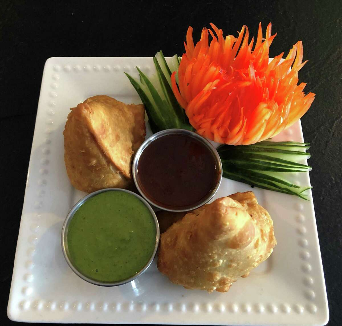 Spectrum/Vinjith Vikaram and Sagar Ahuja are the new owners of Tandoori Flames at 471 Danbury Road in New Milford. Plated above are vegetable samosas, seasoned potato fritters with peas. May 2019