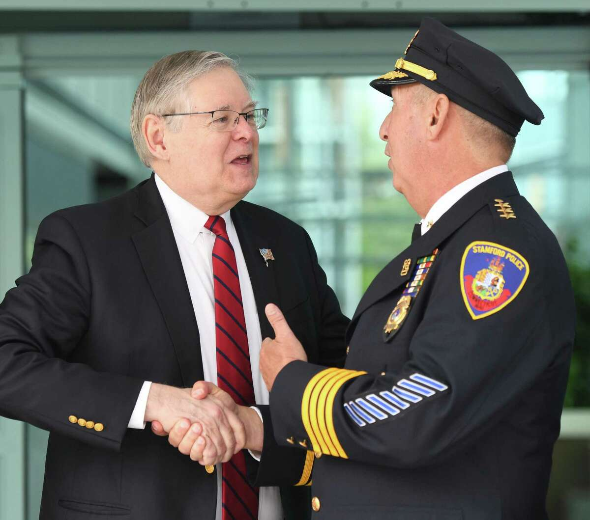 Stamford Mayor David Martin, left, shakes hands with Police Chief Jonathan Fontneau in this undated file photo.