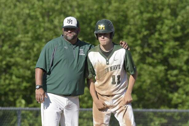 New Milford coach Ryan Johnson talks with Luke Pliego after he reached third in a March 29, 2018, game against Greenwich in New Milford.