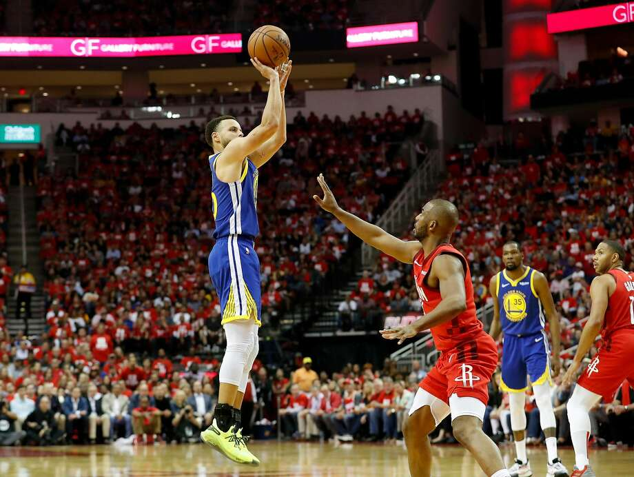 Defended by the Rockets' Chris Paul, Steph Curry hoists a shot. Photo: Tim Warner / Getty Images