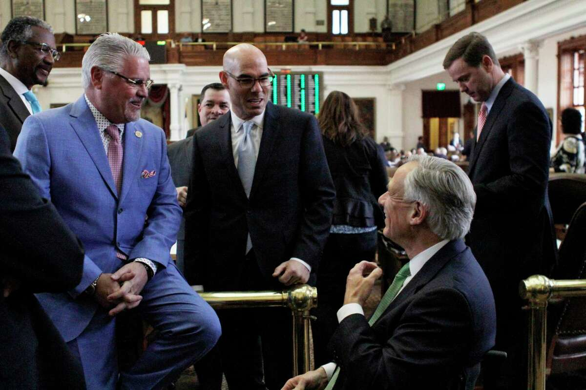 State Rep. Dan Huberty, left, R-Houston, speaks with Texas House Speaker Dennis Bonnen and Texas Gov. Greg Abbott, right, before the chamber debates a bipartisan school finance bill that would pour $9 billion into the state's public education system Wednesday, April 3, 2019, in Austin, Texas. (AP Photo/Clarice Silber)