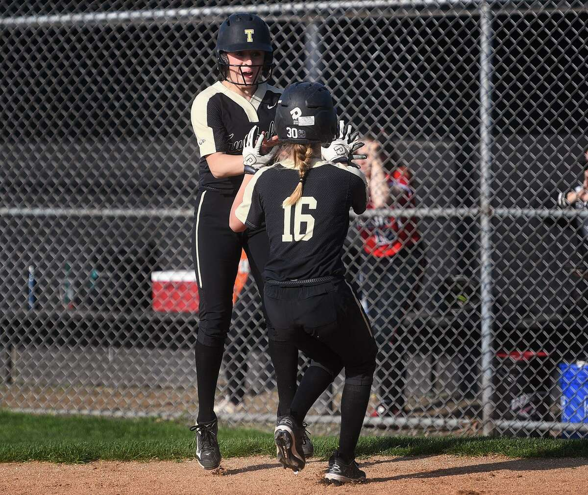 Trumbull's Maggie Coffin, left, high fives teammate Kiley Barbagallo as she crosses home plate in a five run second inning during their softball game with Fairfield Warde at Trumbull High School in Trumbull, Conn. on Tuesday, May 7, 2019.