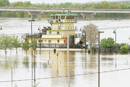 "It almost appeared Tuesday as if the towboat ""Sir Richard"" was parked in the park in Alton. The floodwaters from the Mississippi River dropped an inch or so Tuesday after cresting Monday evening but it still seemed to be hard to tell where Riverfront Park stopped, and the river began. The river is expected to fall a little more before predictions call for a second crest late this weekend or early next week."