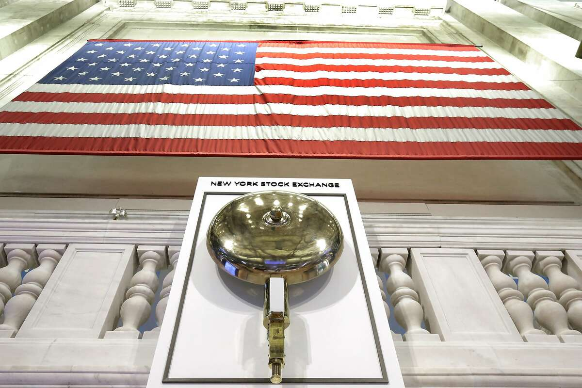 FILE- In this May 17, 2018, file photo an American flag hangs above the bell podium on the floor of the New York Stock Exchange. The U.S. stock market opens at 9:30 a.m. EDT on Wednesday, May 1, 2019. (AP Photo/Richard Drew, FIle)