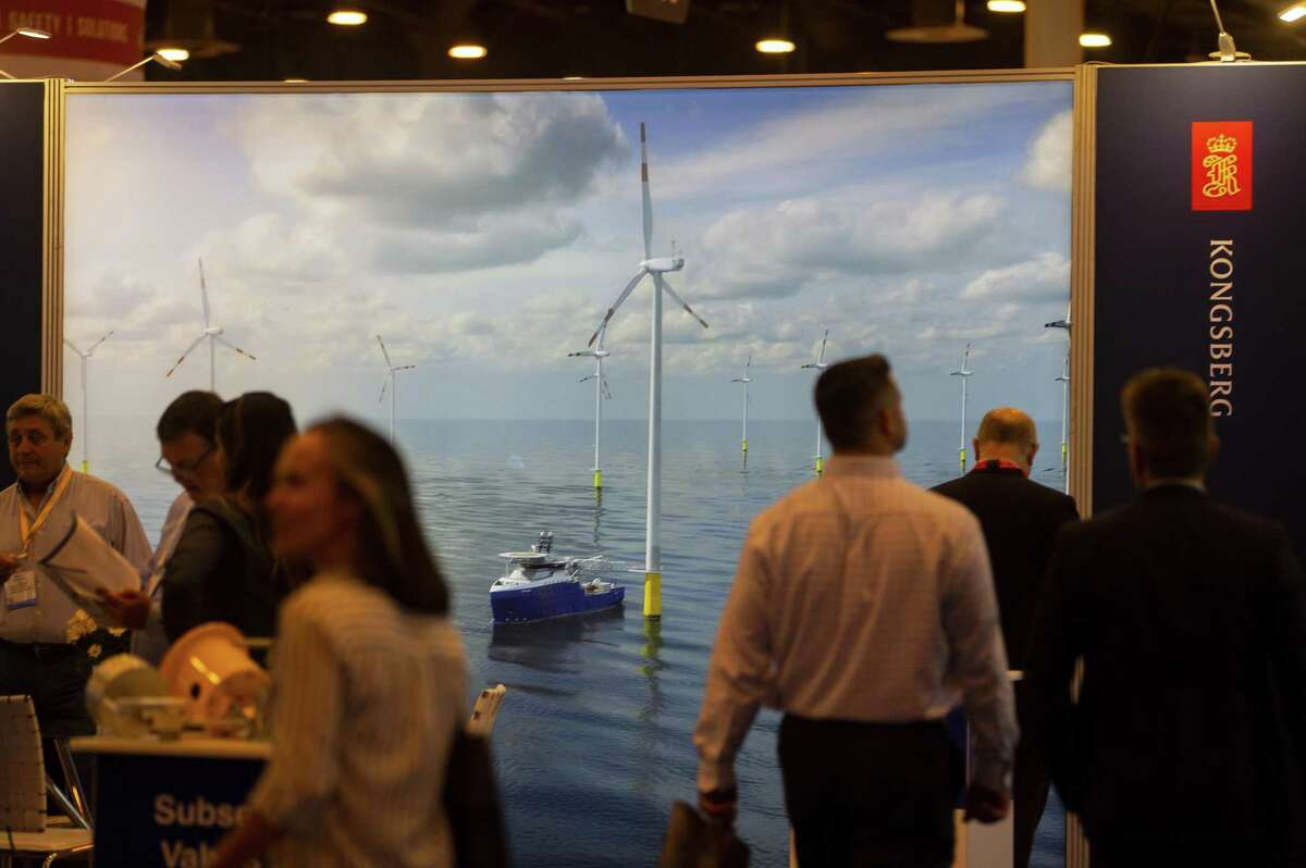 Attendees walk past the Kongsberg display that highlights offshore wind turbines during the annual Offshore Technology Conference inside Houston's NRG Center, Tuesday, May 7, 2019.