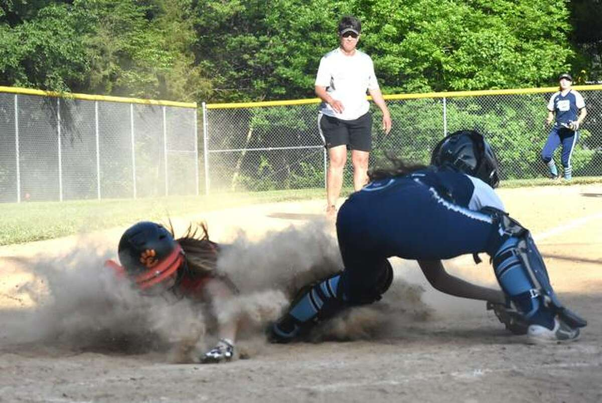Edwardsville's Jayna Connoyer slides safely into home plate to give the Tigers a 6-1 lead over Belleville East.