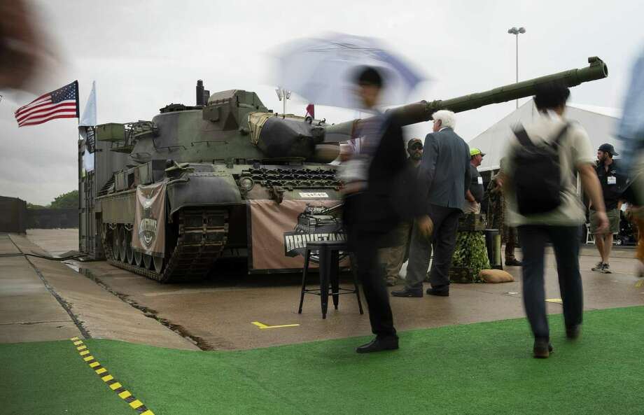 People walk past a tank on display outside the annual Offshore Technology Conference inside Houston's NRG Center, Tuesday, May 7, 2019. Photo: Mark Mulligan,  Houston Chronicle / Staff Photographer / © 2019 Mark Mulligan / Houston Chronicle