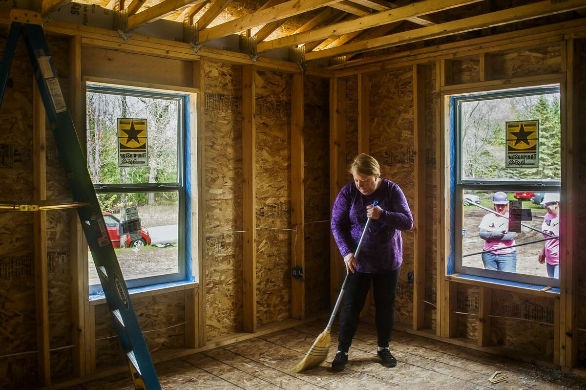 Pat Koehler sweeps debris from the floor inside her future home, which is being built by Midland County Habitat for Humanity for its annual Women Build Week project, on Tuesday, May 7, 2019 in Midland. (Katy Kildee/kkildee@mdn.net)