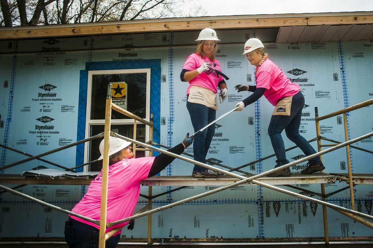 Deanne Marszalkowski, left, passes a piece of siding to Sherry Hodges, right, as Dana Curnutt, center, holds a hammer while the women work on a house being built by Midland County Habitat for Humanity for its annual Women Build Week project on Tuesday, May 7, 2019 in Midland. (Katy Kildee/kkildee@mdn.net)