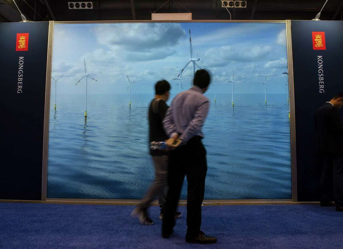 Attendees walk past the Kongsberg display that highlights offshore wind turbines during the annual Offshore Technology Conference inside Houston's NRG Center. Norwegian companies, such as Kongsberg, are on leading edge of making the energy industry smarter, cleaner and better connected through digital technology.
