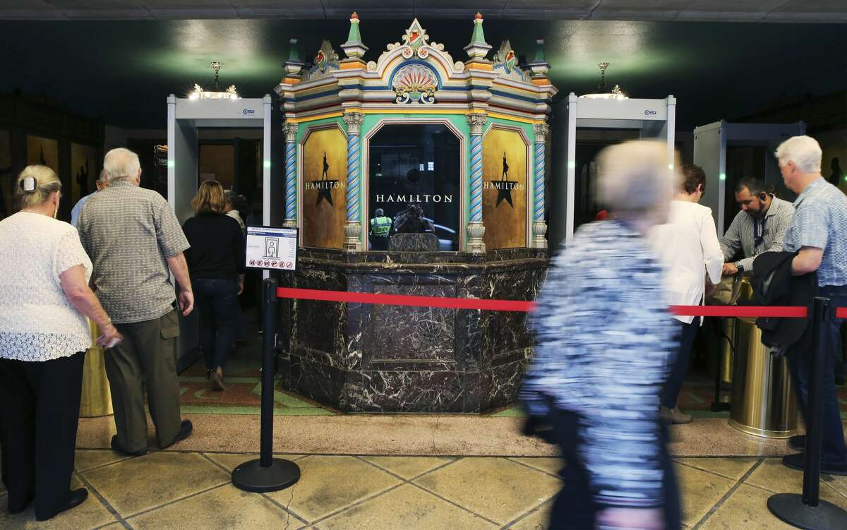 A long line of show-goers go through security detection before entering the Majestic Theater for the opening of the show